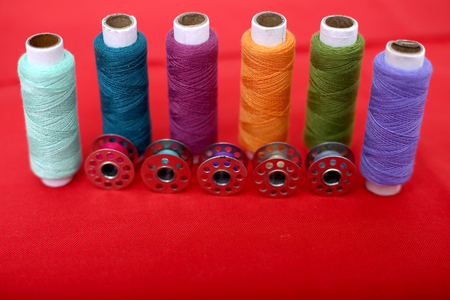 Picture of sewing thread and bobbin on the red cloth.