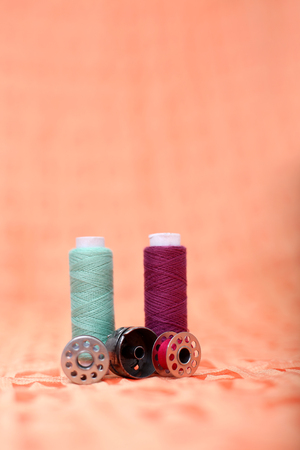 Bobbin case, bobbin and sewing thread on the orange cloth.