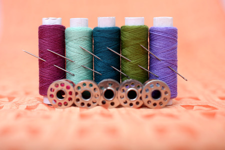 Photo of multicolored sewing thread, needle and bobbin on the orange cloth. Banque d'images