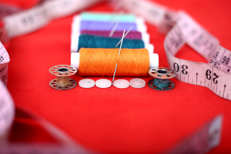 Portrait of threads, needles, bobbin, measure tape and button. Isolated on the red background.
