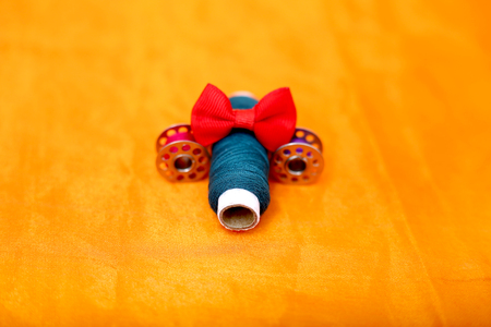 Portrait of sewing threads, red bow and bobbin. Isolated on the red background.