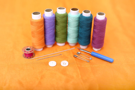 Picture of multicolored sewing thread, needle, bobbin, button, safety pin and needle ripper. Isolated on the yellow background. Banque d'images