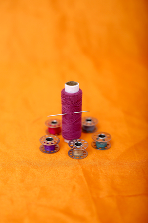 Portrait of bobbin, thread and needle . Isolated on the yellow background.