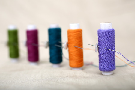 Picture of sewing thread and needle on the cloth.