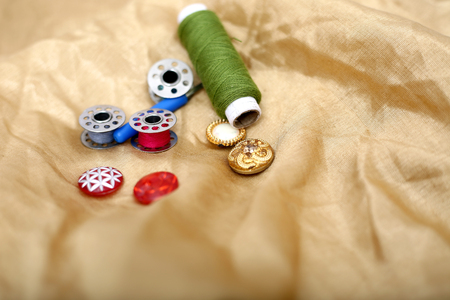 Picture of sewing thread, needle ripper, button and bobbin on the golden cloth. Banque d'images