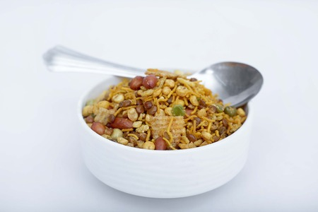 Photo of fried mix namkeen in the bowl. Isolated on the white background. Stockfoto