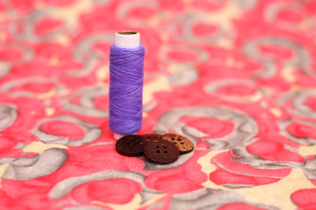 Photo of purple sewing thread and four button. Isolated on the colorful background. Banque d'images