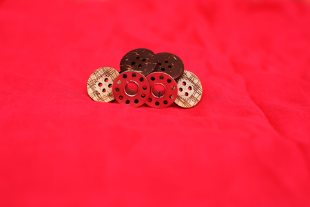 Photo  of bobbin and button. Isolated on the red background. Banque d'images