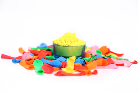 Picture of organic colors and many water balloons for holi festival. Isolated on the white background.