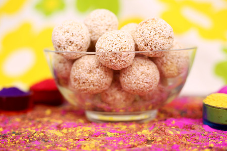 Picture of organic holi color with cholai ke ladoo in the bowl. Isolated on the colorful background.