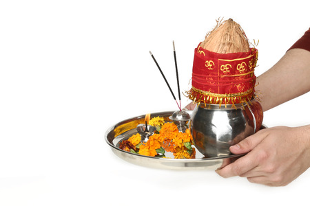 Portrait of hand is holding pooja thali for navratri festival. Isolated on the white background.