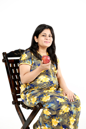 Pregnant lady is holding apple in hand. Isolated on the white background.