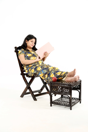Young pregnant woman is reading baby magazine with sitting on the chair. Isolated on the white background.