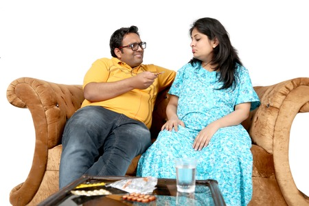 Man is holding medicine in hand and pregnant irritate wife is seeing medicine. Isolated on the white background.