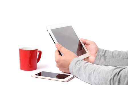 Picture of man working on tablet with mobile and cup. Isolated on white background.
