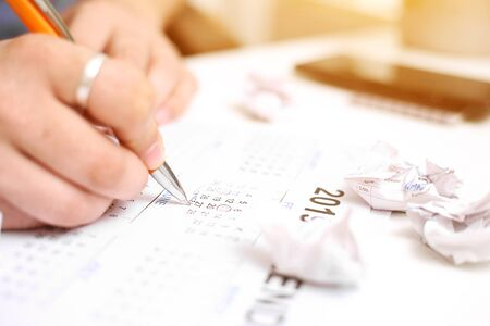 Picture of Man holding Calendar and marking on date. Isolated on white background.
