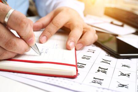 Foto van man schrijven op notebook met mobiel. Geïsoleerd op een witte achtergrond.