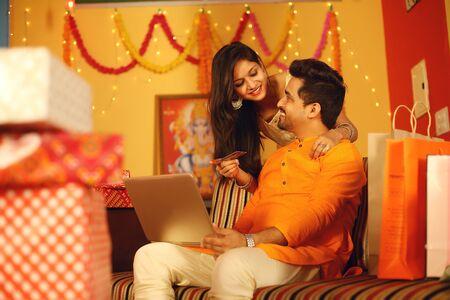 Indian couple is Celebrating Diwali. Isolated on decorative background. Stock Photo