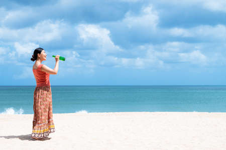 A woman drinks in the sea in summer