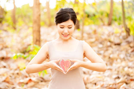 A woman with a red heart mark in nature Stock Photo