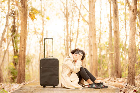 a woman sitting next to a suitcase and holding her head