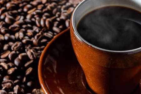 Hot coffee in a cup and coffee beans in the background