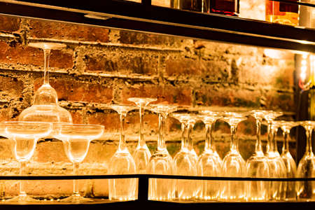 a glass lined up on a shelf with a brick wall in the background at a bar 写真素材 - 156750214