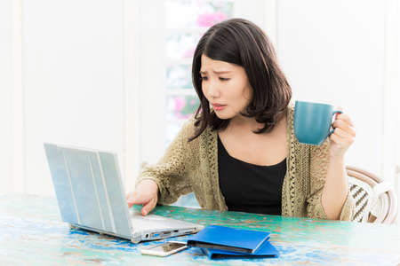 A woman who is worried about looking at a computer Banco de Imagens