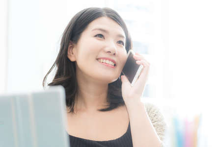 A woman who operates a computer and a smartphone