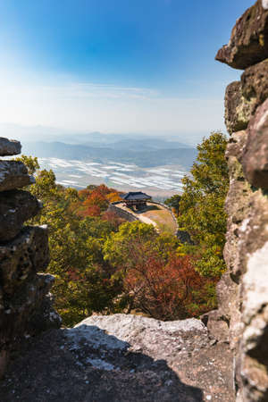 Beautiful Korean autumn scenery. Colorful autumn leaves seen from the top of the mountain and traditional buildings along the castle road. Jeollanam-do, Geumseongsanseong, South Korea.