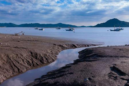 Beautiful reflections of tidal flats on the sea shore. Landscape of fishing boats floating in the sea. Ganghwado Island, Incheon, South Korea. Stock Photo