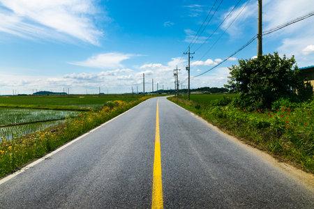 Rural asphalt road through the countryside on a summer day. Ganghwa-gun, Incheon, South Korea
