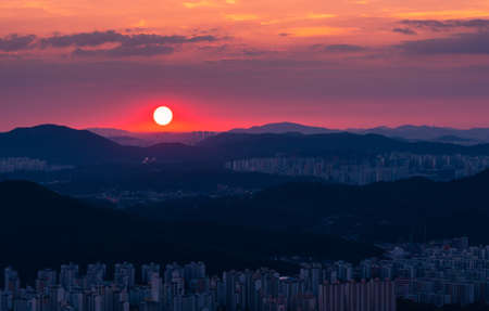 Beautiful red sunset landscape in the city. Hoamsan Mountain in Seoul, South Korea.
