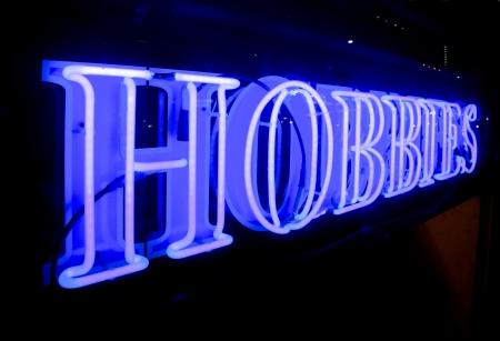 boring frame: A bright blue sign saying HOBBIES, at night Stock Photo
