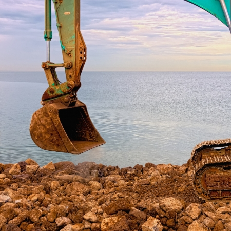 excavator digging rocks by the sea Stock Photo - 19802060