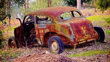 rusty old vintage car in a state  of partial demolision photo