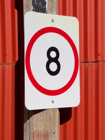 eight kmhr speed restriction sign on red corrugated background  Stock Photo