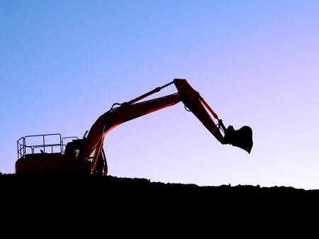 Silhouette of a bulldozer on a ridge with blue mauve sky background photo