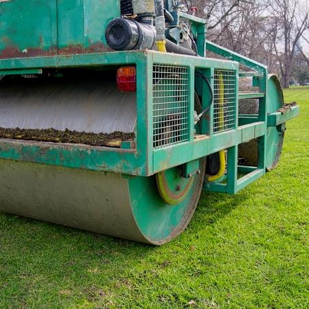 large green grass rolling machinery sitting idle on field  Stock Photo