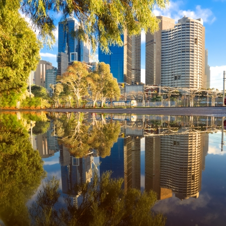 melbourne city buildings reflected in a puddle