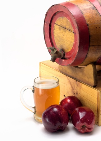 barrel of apple cider with glass and three apples photo