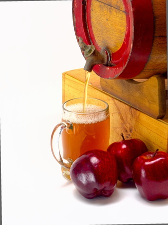 apples cider being poured into a glass from an oak barrel photo