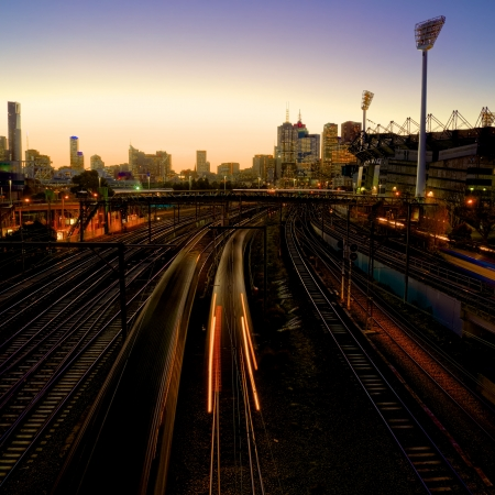 trains at dusk heading past the sporting district in Melbourne