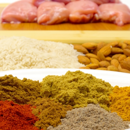 varied ingredients to make chicken korma including spices almonfs and rice photo