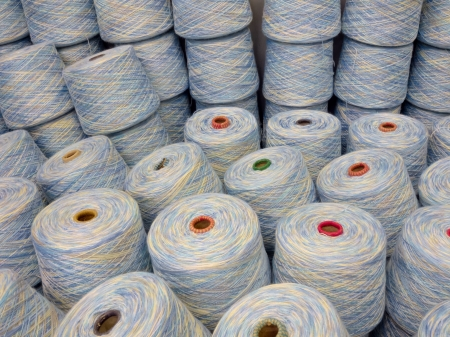stacks of spools of multi coloured yarn in pastel shades Stock Photo