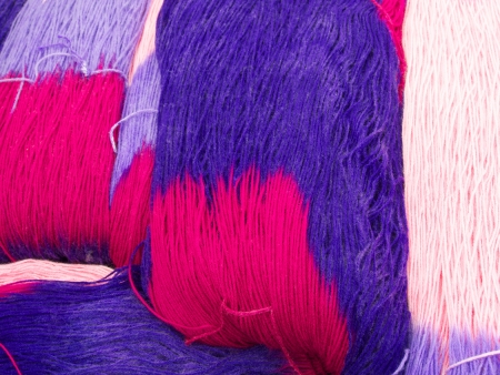 striped skeins of wool in hot pinks and purples