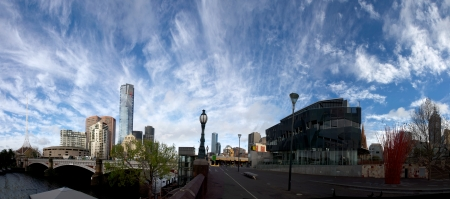 panorama of Melbourne city across bridge with wispy clouds overhead  photo