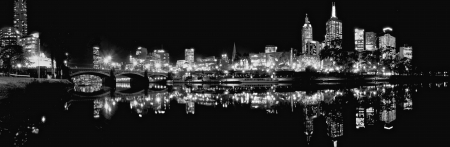 black and white panoramic skyline of melbourne at night reflected in the yarra river