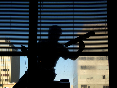 window cleaner seven stories up in silhouette