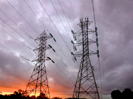 Powerlines delivering high voltage electricity at sunriise